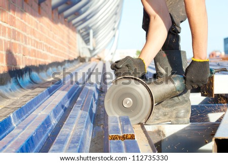 Construction worker sawing steel sheet with trapezoidal profile during roofing works