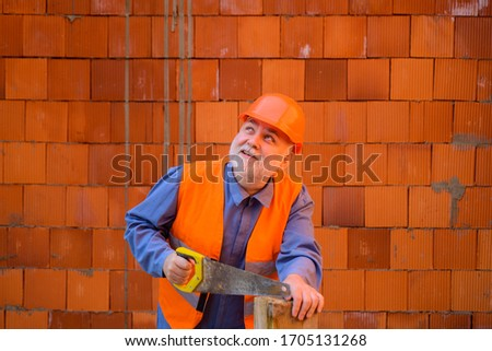 Construction worker sawing with hand saw. Handyman with hand-saw. Carpentry work. Builder worker carpenter handyman with saw. Wood sawing with handsaw. Carpentry service. Builder Sawing with hand saw.