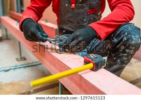 Construction worker screws bolts up tight on the stud on the wooden block in apartment that is under construction, remodeling, renovation, overhaul, extension, restoration and reconstruction. Concept