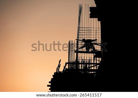 Construction worker silhouette on a construction site at sunset