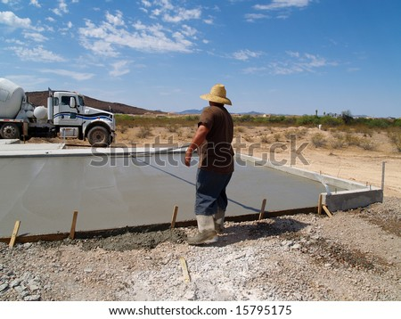 Construction worker smoothing out a freshly poured concrete slab. Shot is set in a desert with a white cement truck in the background. Horizontally framed shot.