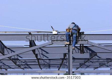 Construction worker straddling a steel beam of a building.