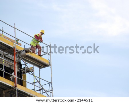 Construction worker talking on cellular phone on scaffolding