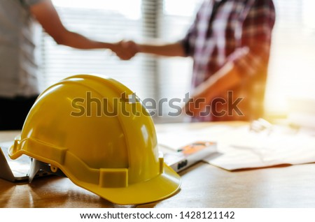 construction worker team hands shaking greeting start up plan new project contract behind yellow safety helmet on workplace desk in office center at construction site, partnership, contractor concept