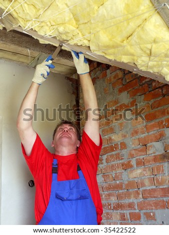 Construction worker thermally insulating house attic with rockwool