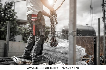 Construction worker unloads rebar from truck and hangs the load on the crane's chains