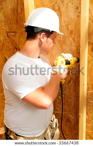 Construction Worker Using A Power Drill To Build A Wall