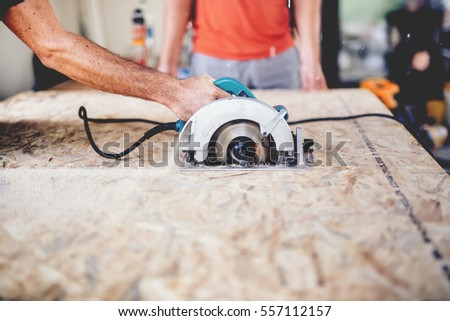 Construction worker using slider compound mitre saw or circular saw for cutting massive wood board. Details of construction, renovation works  #557112157