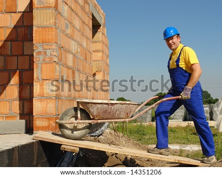 Construction worker wearing blue overall and helmet going inside unfinished brick wall building with wheel-barrow - stock photo