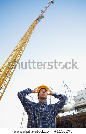 construction worker wearing hard hat. Low angle view, copy space - stock photo