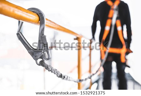 Construction worker wearing safety harness and safety line working at high place. Working at height equipment. Fall arrestor device for worker with hooks for safety body harness
