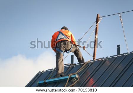 Construction worker wearing safety harness and safety line working on a pitched roof
