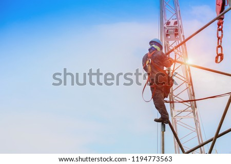 Construction worker wearing safety harness and safety line working on high with scaffolding with equipment protective on crane background