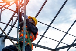 Construction worker wearing safety harness belt during working at high place,The harness is an attachment between a stationary and non-stationary object and is usually fabricated from cable or webbing