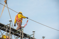 Construction worker wearing safety work at high uniform on scaffolding at construction site