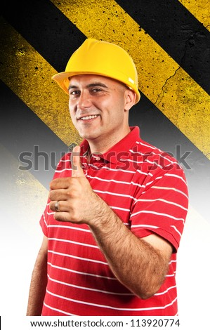 Construction worker wearing yellow hard hat safety equipment. Safety stripes in background.