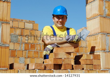 Construction worker wearing yellow t-shirt and blue helmet holding stainless steel trowel resting on brick wall