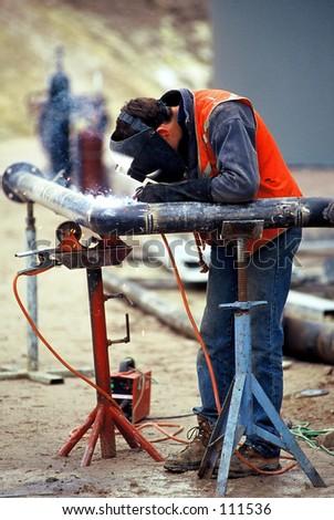 Construction worker welding pipe