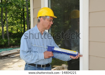 Construction worker with a caulking gun