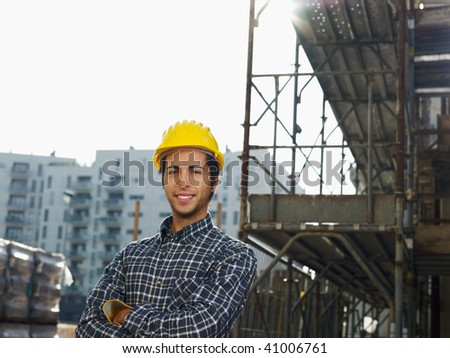 Construction worker with arms folded looking at camera. Copy space