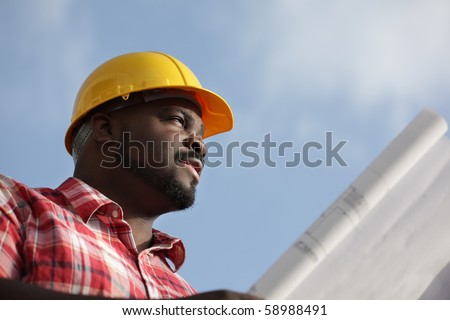 Construction worker with blueprints on a sky background - stock photo