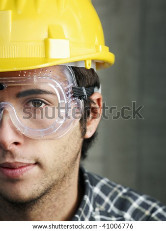 Construction worker with goggles looking at camera. Copy space