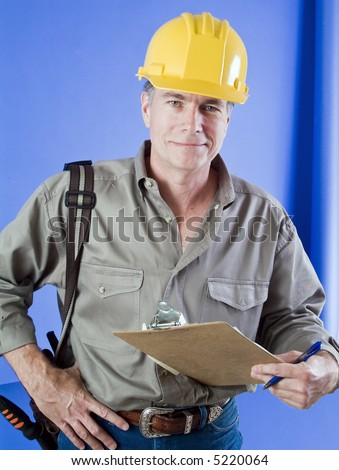 Construction worker with hard hat and clip board standing in front of a bright blue wall.