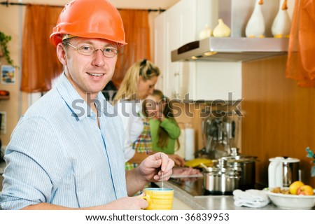 Construction worker with hardhat and father of a family having a morning cup of coffee before heading for his workplace