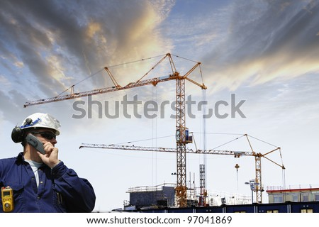 construction worker with large building site in background, sunset