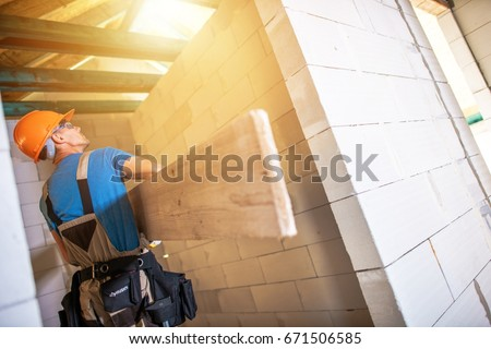 Construction Worker with Large Plank. House Building Project. Construction Business.