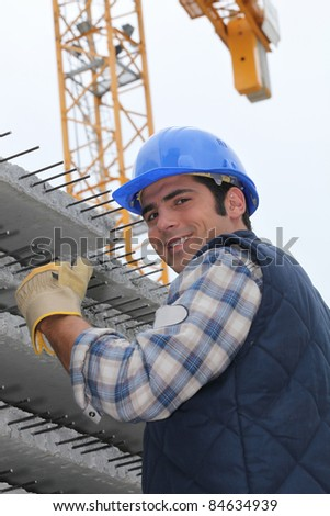 Construction worker with slabs of reinforced concrete