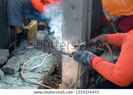 Construction worker with small piling, Concrete foundation pile head (micropile), hammered Into the soil for building construction work