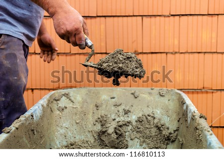 construction worker with trowel on walls of a shell in solid construction. representative photo of the black economy and community care