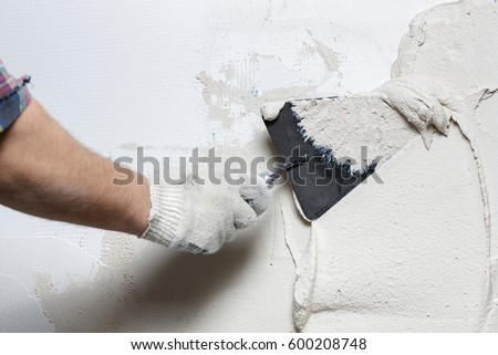 Construction worker with trowel plastering a wall #600208748