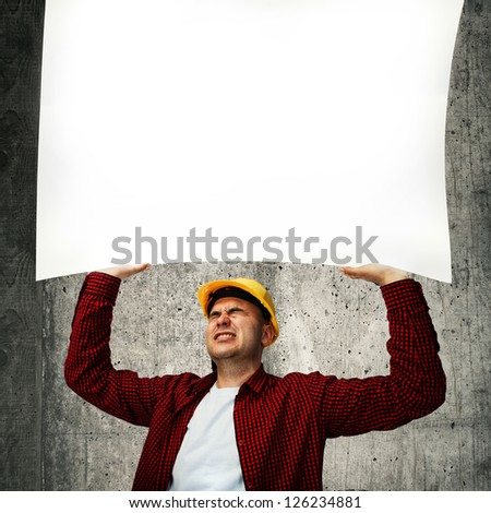 Construction worker with yellow hard hat in red shirt holding a whiteboard above his head.