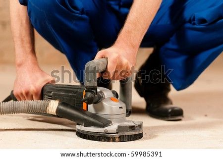 Construction worker working grinding the cement floor