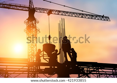 Construction workers and engineers working on high security near the tower crane. Heavy industry and Safety at Work concept.