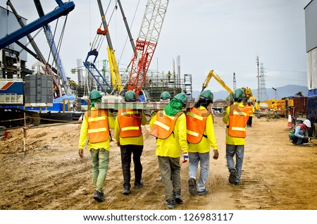 Construction workers are bearing wood, to be unity