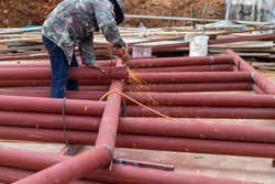 Construction workers are using grinding machines on large steel pipes. Used as a roof pole. Sparking while working Red painted steel pipe To prevent rust and look beautiful