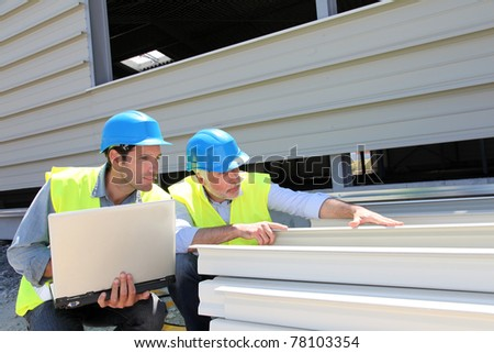 Construction workers checking building material