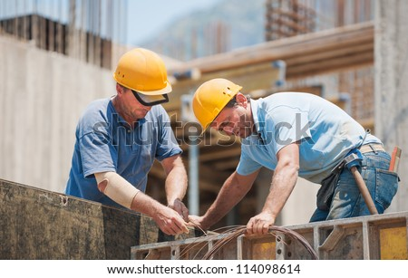 Construction workers collaborating in the installation of cement formwork frames