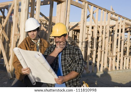 Construction workers discussing above holding blueprints