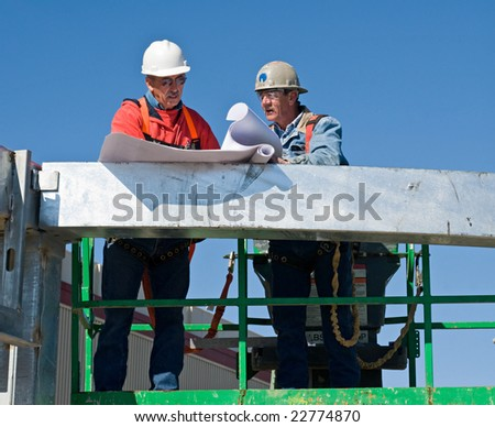 Construction Workers Discussing the Blueprints