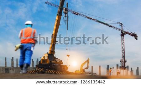 construction workers engineer working in construction site under view of crane excavator in sun set background
