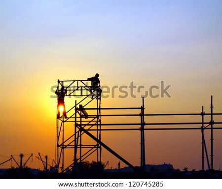 Construction workers high up on a scaffold seen against the setting sun