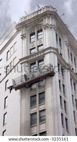 Construction workers in gondola restoring urban building facade