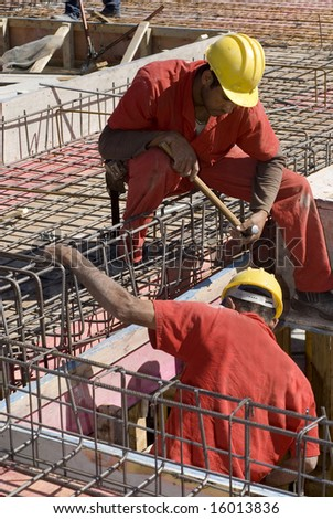 Construction workers install rebar during building construction. Vertically framed photo.