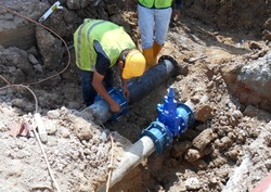 Construction workers install underground utility and services pipe. Trenches was dig to the required level for them to lay the pipes.