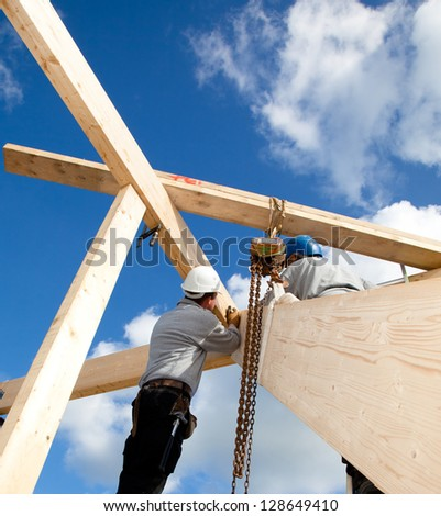 construction workers making a wooden  roof construction