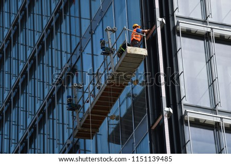 Construction workers on a suspended platform on a skyscraper glass facade Foto d'archivio ©